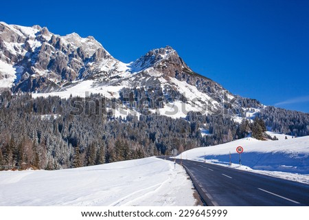 Panorama of winter in the Austrian alps mountain. Asphalt road among snow. - stock photo