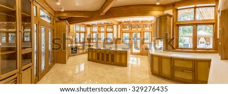 Panorama of wooden kitchen and marble floor in country house. The room is bright and large, new and modern design. In windows views green garden.