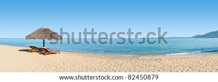 Panorama on the beach with two  deck-chairs in front of the lagoon - stock photo