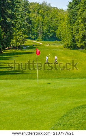 Panorama, outlook at the beautiful golf course with red flag in a sunny day. Canada, Vancouver. Vertical. - stock photo