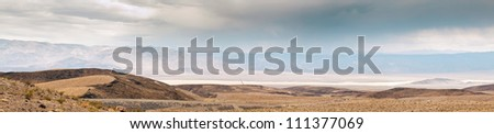 Panorama photo of the great landscape of Death Valley with dramatic cloudy sky. Desert. USA, California. - stock photo