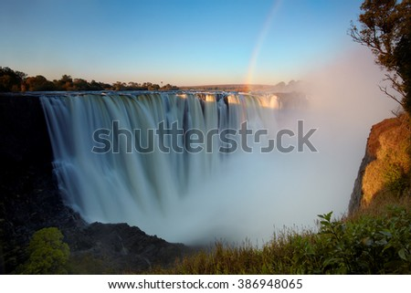 Panorama photo of  Victoria Falls or Mosi-oa-Tunya, waterfall on Zambezi river in very high flow from viewpoint 5  in late evening light with rising spray and intensive rainbow over falls.  - stock photo