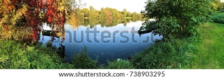 Panorama picture of an Autumn mood and a boat at the river