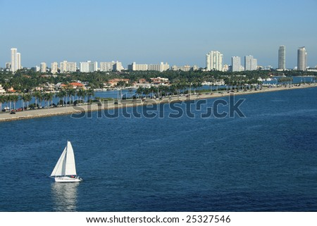 Panorama shot of South Beach Florida.  Sailboats, palm trees, and office buildings all populate the scene. - stock photo