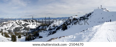 Panorama shot of the Lake Tahoe ski resort at Lake Tahoe, California. A line of skiers is snaking towards the slope with communications tower in the background.