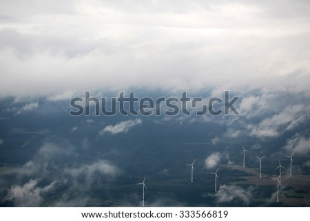 Panorama spectacular skyline view of cloudy blue sky from airplane window over windfarm landscape background wind turbines renewable power energy stations, horizontal picture  - stock photo