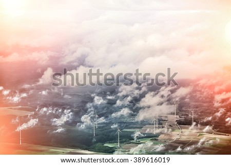 Panorama spectacular skyline view with light-exposed spot of cloudy blue sky from airplane window over windfarm landscape background wind turbines renewable power energy stations, horizontal picture  - stock photo