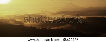 Panorama view into autumn deep misty valley in Bohemian national park, Europe. Trees and hills increased from morning foggy background. Colorful misty above horizon.  - stock photo