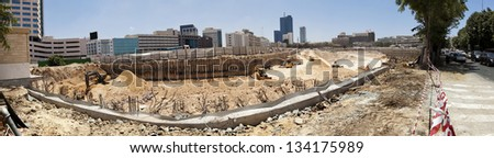 Panorama view of a very large scaled construction site in its primary stage - digging the foundations. It'll be a residential / commercial sky scrapers complex. At the center of Tel-Aviv, Israel. - stock photo