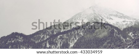 Panorama view of distant mountain peak covered by clouds and snow under overcast sky with conifer trees in the foreground - stock photo