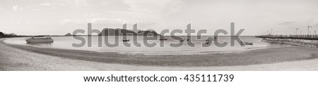 panorama view of sea and beach with traditional boat, bridge, long mountain in background, black and white, brown vintage picture style. Grain added