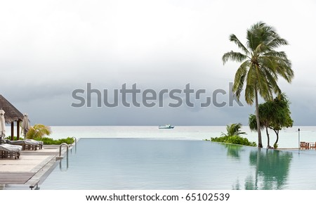 panorama view of swimming pool in maldives island resort. - stock photo