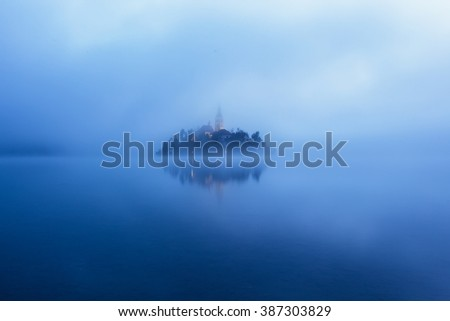 Panorama view of the famous island with old church in the city of Bled (Blejsko jezero). Dreamy scene with mist and cold colors. Slovenia, Europe - stock photo