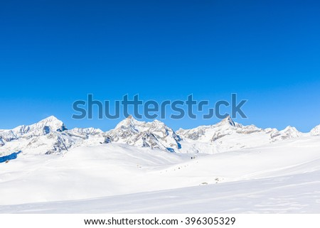 Panorama view of the Pennine Alps on the Italian-Swiss border near Zermatt, Switzerland. A paradise for hiking, skiing, snowboarding and other winter sports. - stock photo