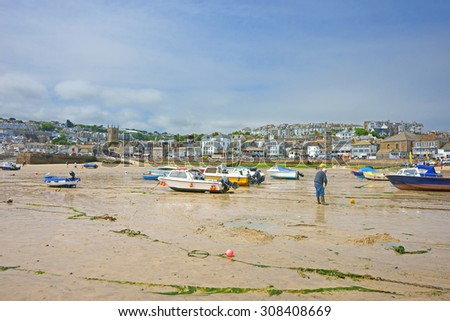 Panorama view of the popular North Cornish fishing town of St Ives and its Harbor at low tide with several, mainly fishing boats, waiting for high tide, Cornwall, United Kingdom - stock photo