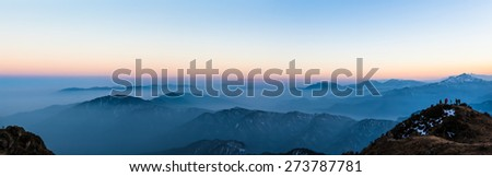 Panorama view of the twilight with silhouette of mountains and cloudscape on top of Cattle Back Mountain (Niubeishan) in Sichuan Province, China - stock photo