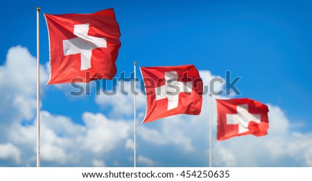 Panorama view of three national flags of Switzerland waving in the sunshine against blue sky and clouds at First of August, the national holiday of the Swiss Confederation - stock photo