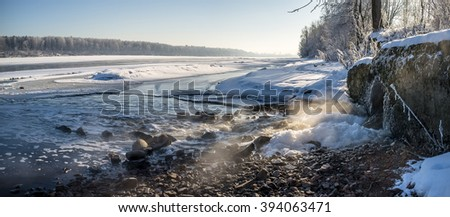 Panorama view of water pours from the the waste-pipe into the river in winter, on a background of snow-covered beaches and nature - stock photo