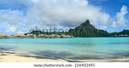 Panorama view on luxury overwater bungalows in a vacation resort in the blue lagoon with in the background the tropical island of Bora Bora, near Tahiti, in the pacific archipelago French Polynesia. - stock photo