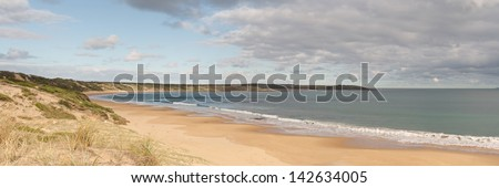 Panorama with calm water and empty sandy beach at Philip Island  with clouds over blue sky in Victoria, Australia - stock photo