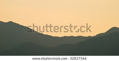 Panorama with golden sky and misty mountains at sunset in Japan