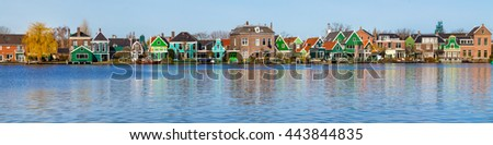 Panorama with row of old dutch green traditional houses in town Zaanse Schans in Netherlands, North Holland near Amsterdam - stock photo