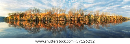 panorama with the autumn trees and clouds - stock photo