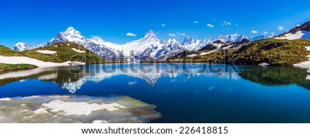 Panorama with Wetterhorn, Schreckhorn, and Finsteraarhorn peaks reflected in the waters of the Bachalpsee lake, Swiss Alps. - stock photo
