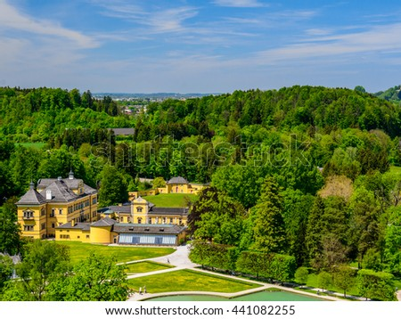 Panoramic aerial view from the mountains - park with pond and numerous fountains under Alps, bright blue sky with clouds, Salzburg, Austria