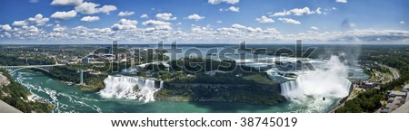 Panoramic aerial view of Niagara Falls, including Canadian and American Falls, Rainbow Bridge, the American frontier, the city of Niagara Falls and the boats of the Maid of the Mist - stock photo