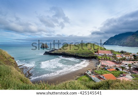 Panoramic aerial view of Porto da Cruz town. Alagoa surfer's beach, rum factory and fortress ruins on the cape. Madeira island north coast, Portugal.