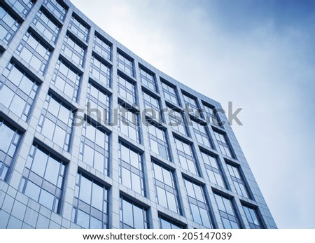 Panoramic and prospective wide angle view to steel light blue background of glass high rise building skyscraper. - stock photo