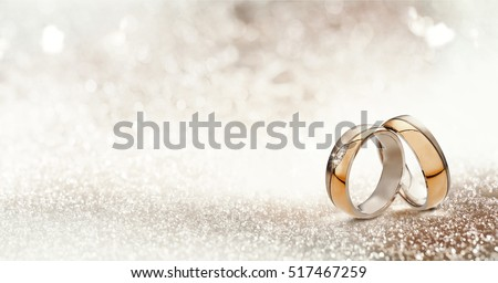 Panoramic banner of two upright gold wedding bands symbolic of love and romance on a textured glitter background with copy space for your greeting or congratulations