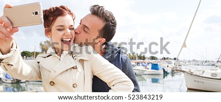 Panoramic beautiful young couple kissing using a smart phone taking selfies pictures, networking on coastal maritime winter holiday, boats marina outdoors. Technology travel lifestyle, sunny exterior.