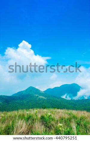 Panoramic bird eye aerial view of beautiful morning sunrise, dramatic cloud of sea, grassland under bright blue sky in Yangmingshan(Yang ming Mountain) National Park in Taiwan - stock photo