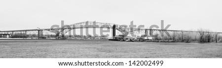 Panoramic black and white photo of the blue water bridge between Port Huron Michigan and Sarnia Ontario. - stock photo