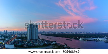 Panoramic cityscape of Bangkok in twilight viewing Rama III road along Chao Phraya river , Thailand