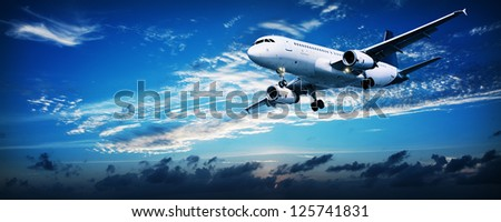 Panoramic composition of a flying jet in a sunset sky - stock photo