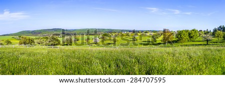 panoramic countryside with fields and blooming trees in the Taunus in Usingen - stock photo