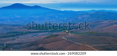 Panoramic format photo of Val D'Orcia valley taken from Pienza, Tuscany Italy. The sun is rising and dissolving the early morning haze in the air, revealing this beautiful landscape. - stock photo