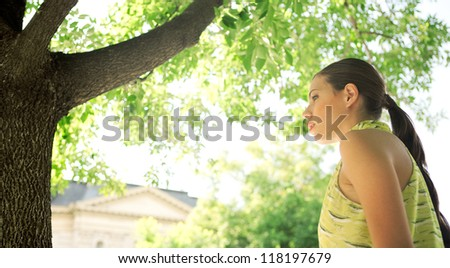Panoramic format portrait of a young professional businesswoman standing near a tree in a classic office buildings financial district city, on a sunny day outdoors. - stock photo