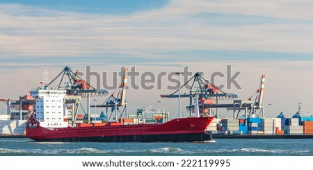 Panoramic image of a container ship passing cranes in Rotterdam harbor - stock photo