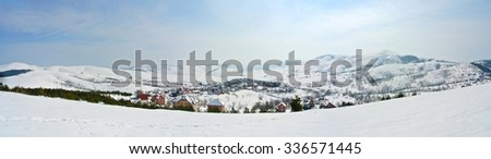 Panoramic image of beautiful, idyllic snowy winter landscape in the mountains, on a crisp sunny morning, with snow-covered rooftops of a small picturesque village.