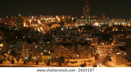 Panoramic image of downtown modern Jerusalem, Israel during the night with the famous bus station and international bank in the back horizon line and a neighborhood in the foreground - stock photo