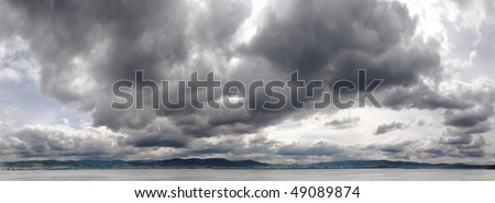 panoramic image of gray storm clouds over river - stock photo