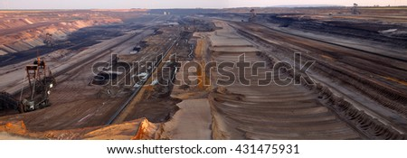 Panoramic image of large bucket wheel excavators digging lignite (brown-coal) in an open cast mine during sunset, Nordrhein-Westfalen, Germany - stock photo