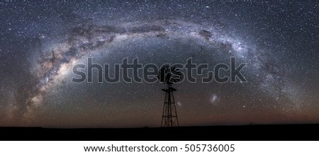 panoramic image of milky way and windmill