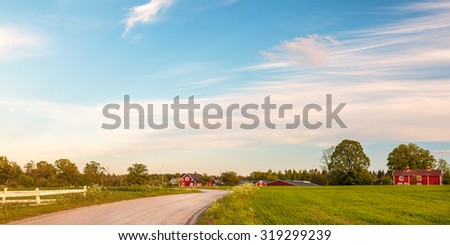 Panoramic image of old red wooden farms with road during sundown in Smaland, Sweden - stock photo