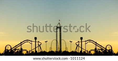 Panoramic image of rollercoaster park at sunset - stock photo