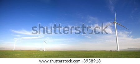 Panoramic image of wind powered electricity generator standing against the blue sky on a wind farm - stock photo